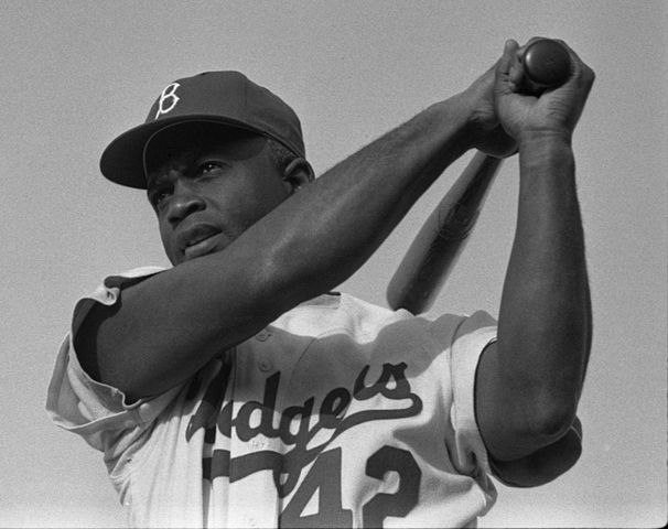 Jackie Robinson swinging a bat in Dodgers uniform, 1954, Photo by Bob Sandberg (domaine public)